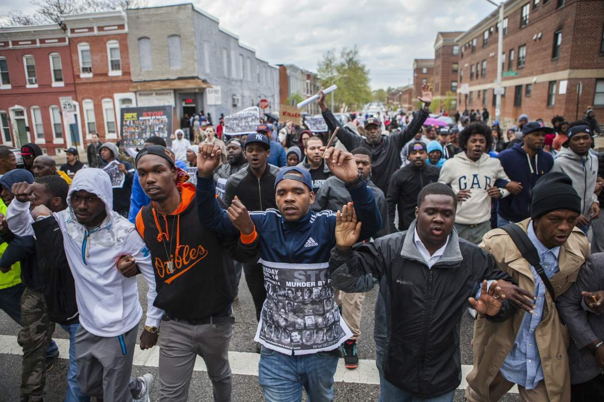 WASHINGTON, USA - APRIL 22: Hundreds of people march through the streets of Baltimore to seek justice for the death for Freddie Gray who died from injuries suffered in Police custody in Baltimore, USA on April 22, 2015. (Photo by Samuel Corum/Anadolu Agency/Getty Images)